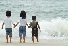 Kinderen die met golven spelen   Stock Afbeeldingen