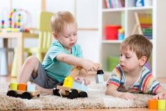 Kinderen die met houten auto thuis of opvang spelen Onderwijsspeelgoed voor kleuterschool en kleuterschooljong geitje Royalty-vrije Stock Fotografie