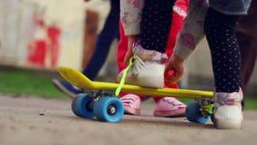 Kinderen die met skateboard spelen en proberen te berijden Jonge geitjes die pret hebben openlucht stock videobeelden