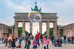 Kinderen die met slagzeepbels spelen voor de Poort van Brandenburg, Berlijn stock foto's