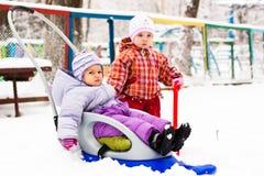 Kinderen die met slee en spade in sneeuw spelen Stock Foto