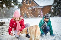 Kinderen die met sneeuw en hond spelen stock foto's