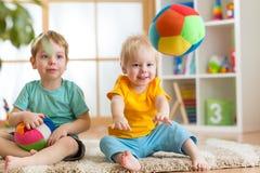 Kinderen die met zachte bal in speelkamer spelen Stock Foto's