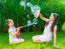 Kinderen die met zeepbeltoverstokje spelen in het park op zonnige su Stock Foto