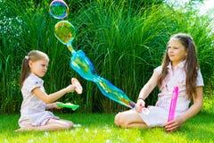 Kinderen die met zeepbeltoverstokje spelen in het park op zonnige su Royalty-vrije Stock Afbeeldingen