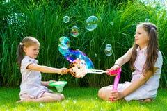Kinderen die met zeepbeltoverstokje spelen in het park op zonnige su Stock Afbeeldingen