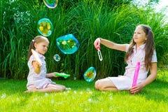 Kinderen die met zeepbeltoverstokje spelen in het park op zonnige su Stock Foto's