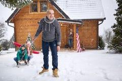 Kinderen die met zijn vader sledding stock foto