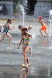 Kinderen die onder fonteinen in Bern spelen Stock Fotografie