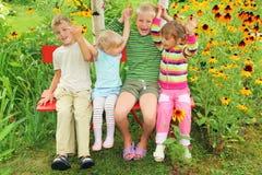 Kinderen die op bank in tuin zitten Royalty-vrije Stock Afbeelding