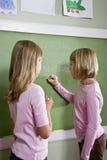 Kinderen die op bord in klaslokaal schrijven Stock Foto