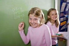 Kinderen die op bord in klaslokaal schrijven Stock Foto's