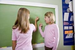 Kinderen die op bord in klaslokaal schrijven stock afbeelding