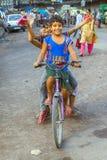 Kinderen die op een fiets vroeg zitten Stock Foto's