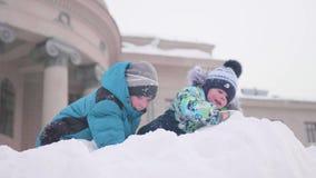 Kinderen die op een sneeuwberg spelen, werpend sneeuw en smejutsja Zonnige ijzige dag Pret en spelen in de verse lucht stock footage