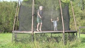 Kinderen die op een trampoline buiten in de zomer springen stock footage