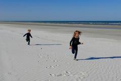 Kinderen die op een wit strand lopen Stock Afbeelding