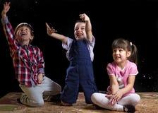 Kinderen die op een zwarte achtergrond spelen Stock Foto's