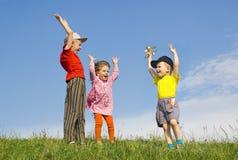 Kinderen die op gras spelen Stock Foto