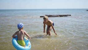 Kinderen die op het overzees spelen, die tot een plons van water leiden Pret en spelen in openlucht stock video