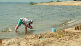 Kinderen die op het strand door de rivier op een zonnige dag spelen stock footage