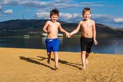 Kinderen die op het zand op het strand in werking worden gesteld stock afbeelding