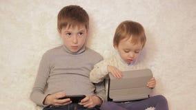 Kinderen die op laag het spelen op uw tablet en telefoon zitten stock videobeelden