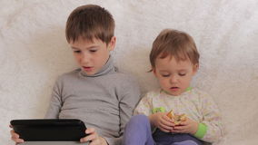 Kinderen die op laag het spelen op uw tablet en telefoon zitten stock video