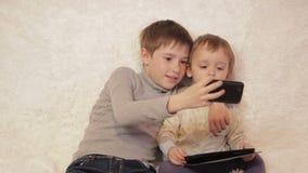 Kinderen die op laag het spelen op uw tablet en telefoon zitten stock footage