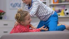 Kinderen die op meisje kietelen en bank, jongen spelen die, onbezorgde kinderjaren lachen stock footage
