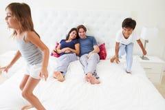 Kinderen die op Oudersbed springen die Pyjama's dragen stock foto