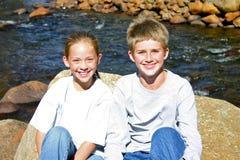 Kinderen die op rotsen door de rivier zitten Stock Foto