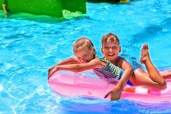 Kinderen die op roze opblaasbare strandmatras bij zwembad zwemmen royalty-vrije stock fotografie