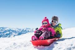 Kinderen die op Sneeuw sledding royalty-vrije stock foto