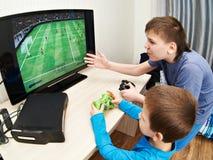 Kinderen die op spelenconsole spelen om voetbal te spelen Stock Fotografie