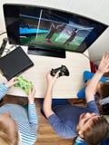 Kinderen die op spelenconsole spelen om voetbal te spelen Stock Foto's