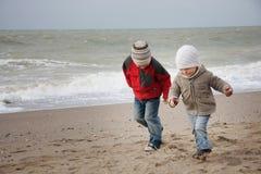 Kinderen die op strand lopen Stock Foto's