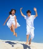 Kinderen die op strand springen Stock Foto's