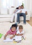Kinderen die op vloer in woonkamer schilderen royalty-vrije stock fotografie