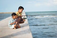 Kinderen die op zee vissen stock foto's