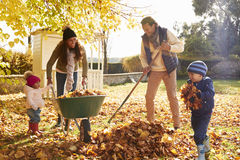 Kinderen die Ouders helpen om Autumn Leaves In Garden te verzamelen Royalty-vrije Stock Afbeelding