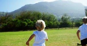 Kinderen die in park tijdens ras lopen stock footage