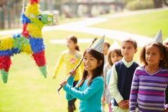 Kinderen die Pinata raken bij Verjaardagspartij stock foto's