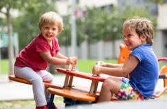 Kinderen die pret hebben bij speelplaats Stock Afbeeldingen