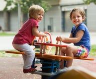 Kinderen die pret hebben bij speelplaats Stock Fotografie