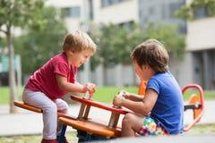 Kinderen die pret hebben bij speelplaats Royalty-vrije Stock Fotografie