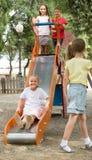Kinderen die pret op dia hebben bij speelplaats Stock Afbeelding