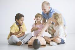 Kinderen die reanimation leren die mannequin gebruiken stock fotografie