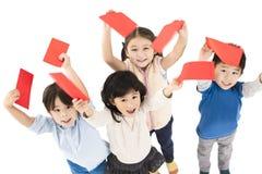 Kinderen die rode envelop voor Chinees nieuw jaar tonen royalty-vrije stock fotografie