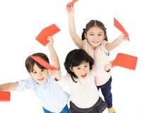 Kinderen die rode envelop voor Chinees nieuw jaar tonen stock foto's